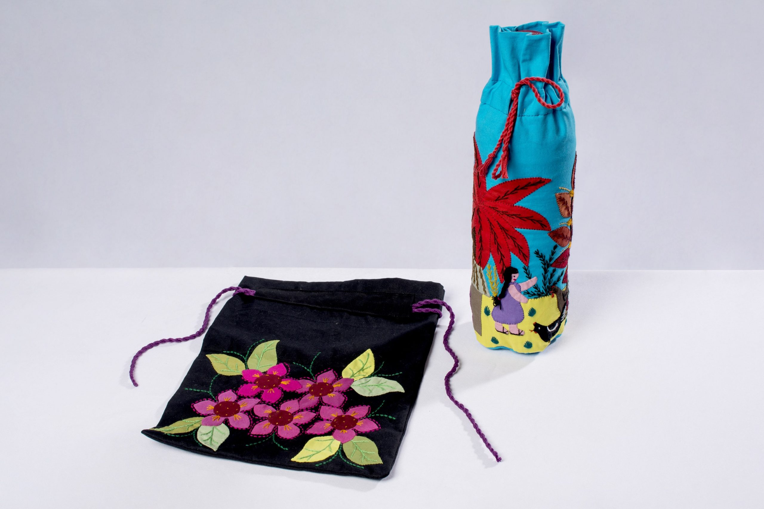 Bolsa con aplicaciones y porta botella (remendado y bordado con diseños de origen Chiquitano).Material: Drill, papelina y nansú.